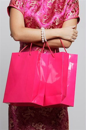 singapore traditional costume lady - Cropped shot of woman wearing pink cheongsam carrying shopping bags. Stock Photo - Premium Royalty-Free, Code: 656-03076309