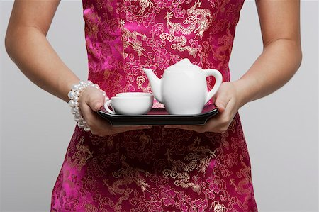singapore traditional costume lady - cropped shot of woman wearing pink cheongsam holding tea Stock Photo - Premium Royalty-Free, Code: 656-03076321