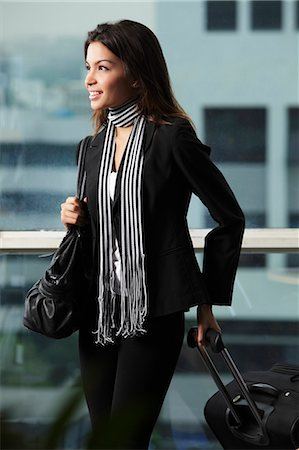 exotic outdoors - Young woman holding bag and pulling suitcase Stock Photo - Premium Royalty-Free, Code: 656-03519533