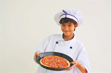 stage show - A boy dressed as a chef holding a pizza Stock Photo - Premium Royalty-Free, Code: 659-06151806