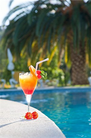 A Tequila Sunrise by a pool with a plam tree in the background Stock Photo - Premium Royalty-Free, Code: 659-06151868