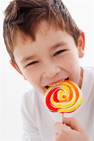 A little boy biting into a lolly Stock Photo - Premium Royalty-Free, Code: 659-06153341