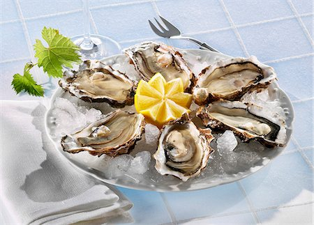 Fresh oysters with lemon on ice Stock Photo - Premium Royalty-Free, Code: 659-06153400
