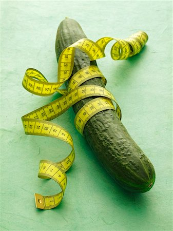slim - A cucumber with tape measure on a green surface Stock Photo - Premium Royalty-Free, Code: 659-06184396