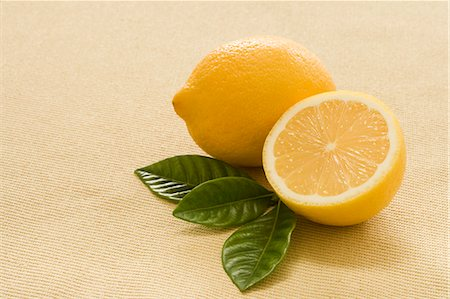 Whole and Half a Lemon with Fresh Tea Leaves Stock Photo - Premium Royalty-Free, Code: 659-06186568