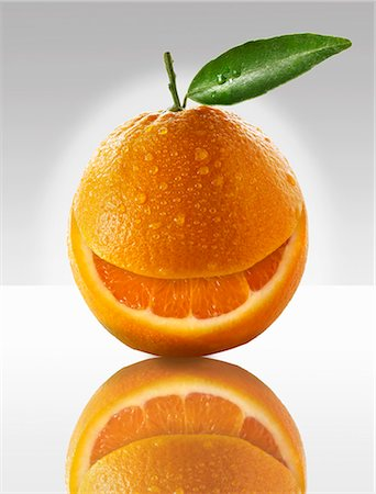 One orange with a slice taken out of it Stock Photo - Premium Royalty-Free, Code: 659-06187911