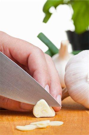 Garlic being sliced Stock Photo - Premium Royalty-Free, Code: 659-06187979