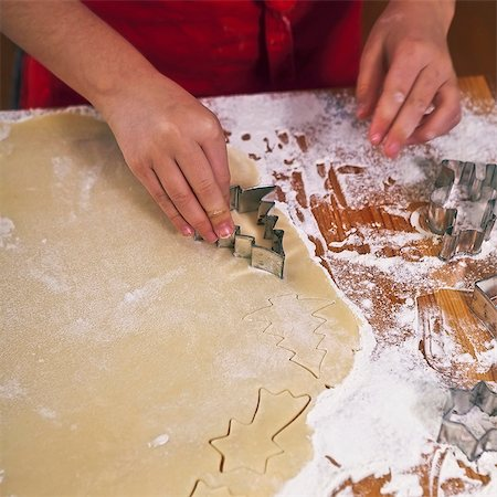 Christmas biscuits being cut out Stock Photo - Premium Royalty-Free, Code: 659-06188554