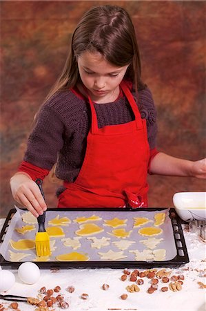 A girl brushing biscuits on a baking tray with egg yolk Stock Photo - Premium Royalty-Free, Code: 659-06188557