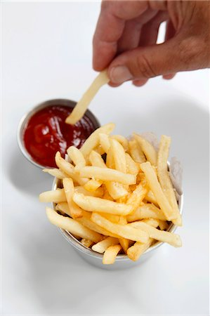 snack - Chips being dipped into ketchup Stock Photo - Premium Royalty-Free, Code: 659-06306938