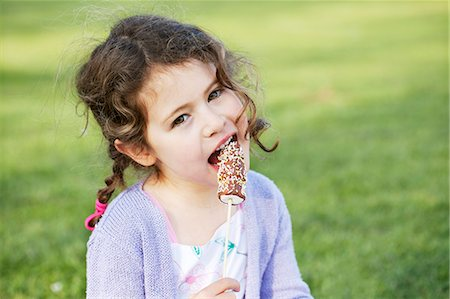 A little girl eating marshmallows Stock Photo - Premium Royalty-Free, Code: 659-06307502