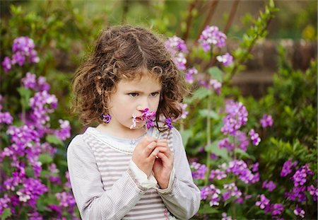A little girl smelling flowers in a garden Stock Photo - Premium Royalty-Free, Code: 659-06307514