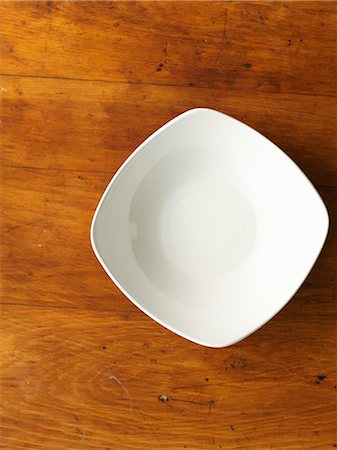 A white porcelain bowl on a wooden surface (seen from above) Stock Photo - Premium Royalty-Free, Code: 659-06307542