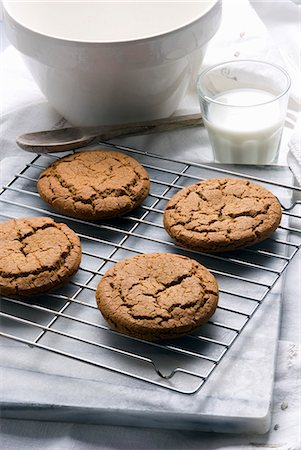 Fresh Homemade Molasses Cookies on a Cooling Rack; Glass of Milk Stock Photo - Premium Royalty-Free, Code: 659-06307604