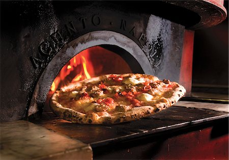 spicy - Pizza In Front of a Wood Fired Oven Stock Photo - Premium Royalty-Free, Code: 659-06372387