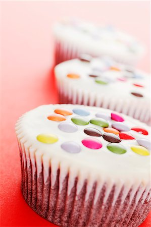 White cupcakes decorated with coloured chocolate beans Stock Photo - Premium Royalty-Free, Code: 659-06372693
