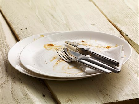 A dirty plate with cutlery and a paper napkin Stock Photo - Premium Royalty-Free, Code: 659-06372721