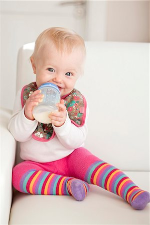 A baby sitting on a sofa with a bottle of milk Stock Photo - Premium Royalty-Free, Code: 659-06373078