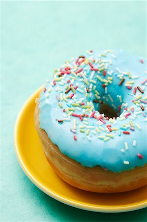A blue-glazed doughnut decorated with sugar sprinkles Stock Photo - Premium Royalty-Free, Code: 659-06373533