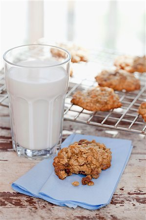 Homemade Oatmeal Cookies with a Glass of Milk; One Cookie with Bite Taken Out; Cookies on Cooling Rack Stock Photo - Premium Royalty-Free, Code: 659-06373669