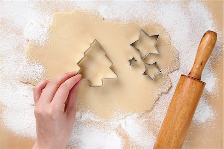 Hand Placing Christmas Tree Cookie Cutter on Rolled Out Cookie Dough; Star Cookie Cutters Stock Photo - Premium Royalty-Free, Code: 659-06373701