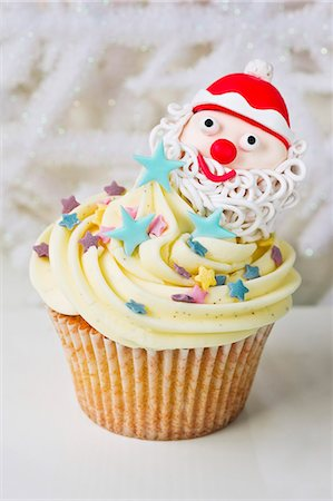 A vanilla cupcake decorated with a Father Christmas and sugar stars Stock Photo - Premium Royalty-Free, Code: 659-06494271