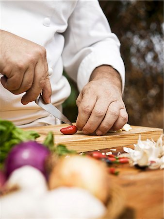 A chef slicing a chilli pepper Stock Photo - Premium Royalty-Free, Code: 659-06494837