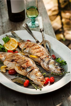 Two Whole Grilled Stuffed Branzino Fish on a Platter; On an Outdoor Table Stock Photo - Premium Royalty-Free, Code: 659-06495114