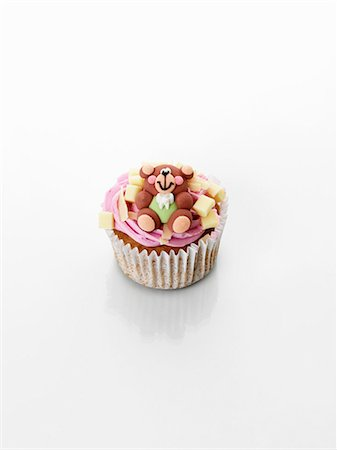 A cupcake decorated with strawberry cream and a teddy bear Stock Photo - Premium Royalty-Free, Code: 659-06493825