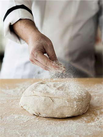 Fresh pizza dough being dusted with flour Stock Photo - Premium Royalty-Free, Code: 659-06671140