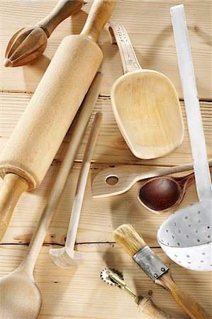 Kitchen utensils on a pale wooden surface Stock Photo - Premium Royalty-Free, Code: 659-06671273