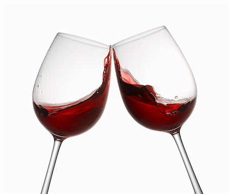 Glasses of red wine being clinked together Stock Photo - Premium Royalty-Free, Code: 659-06671365