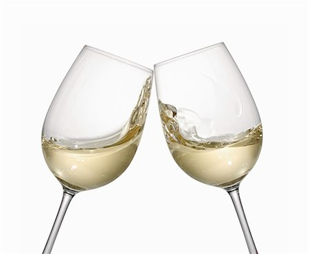 White wine glasses being clinked together Stock Photo - Premium Royalty-Free, Code: 659-06671369