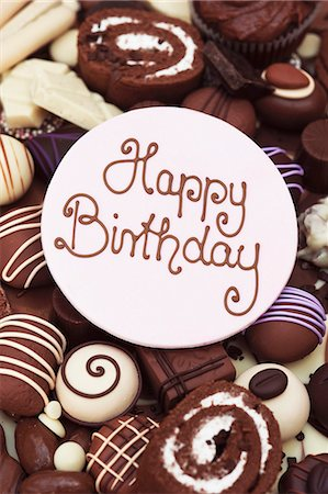 sweets - Happy Birthday lettering on a disc of icing, on top of chocolate cakes and sweets Stock Photo - Premium Royalty-Free, Code: 659-06671399