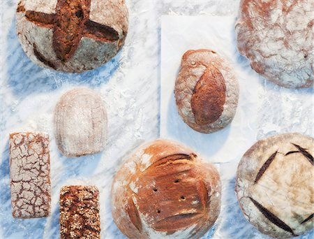 different - A variety of loaves, on paper and on a marble surface, dusted with flour Stock Photo - Premium Royalty-Free, Code: 659-06671597
