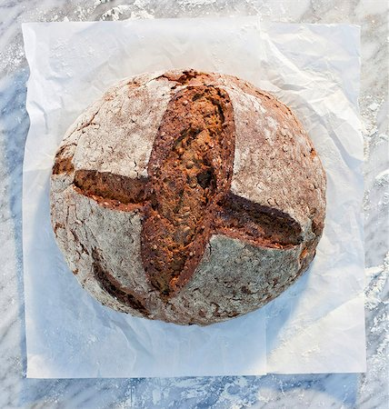 rustic - A rustic loaf of bread on paper, on a marble slab, dusted with flour Stock Photo - Premium Royalty-Free, Code: 659-06671590