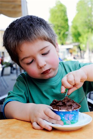 A little boy eating chocolate ice cream in an ice cream cafe Stock Photo - Premium Royalty-Free, Code: 659-06900781