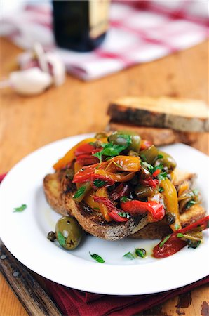 Bruschetta topped with red and yellow peppers, olives and capers Stock Photo - Premium Royalty-Free, Code: 659-06901444