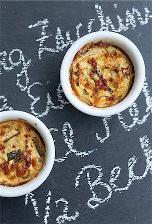 slate - Two Individual Zucchini Casseroles on Chalkboard Surface Stock Photo - Premium Royalty-Free, Code: 659-06901521