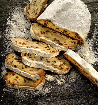 sweet - Christmas stollen dusted with icing sugar, partly sliced Stock Photo - Premium Royalty-Free, Code: 659-06902106