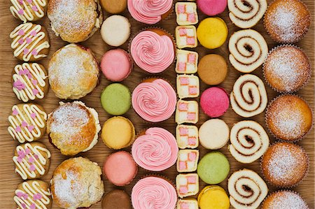sweets - Rows of cupcakes, scones, macarons, Swiss rolls and pieces of mini-Battenburg cake Stock Photo - Premium Royalty-Free, Code: 659-06902202
