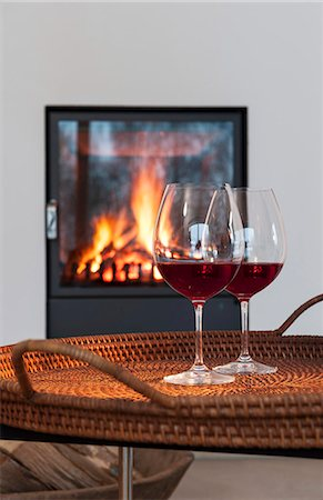 Two glasses of red wine on a table in front of a fireplace Stock Photo - Premium Royalty-Free, Code: 659-06902473