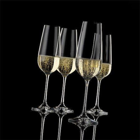 Four champagne glasses in front of a black background Stock Photo - Premium Royalty-Free, Code: 659-06902600