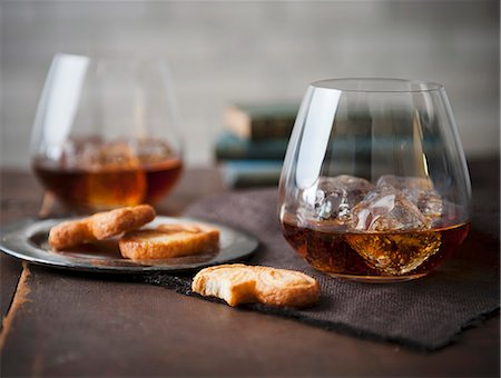 Two Stemless Glasses of Whisky on the Rocks with Cookies Stock Photo - Premium Royalty-Free, Code: 659-06903059