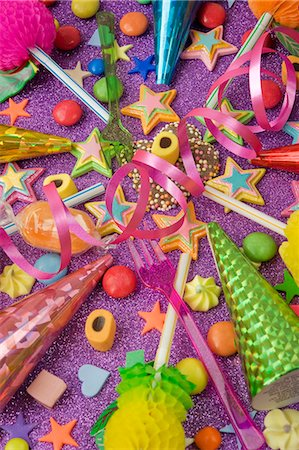 overview still life of various party decorations, party poppers sweets and straws for the party table on a purple glittery table Stock Photo - Premium Royalty-Free, Code: 659-06903144