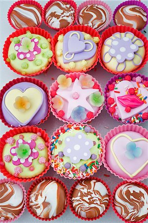 overview o of coloured cup cakes in red and pink plastic cake covers decorated with hearts, lips and sweets Stock Photo - Premium Royalty-Free, Code: 659-06903182