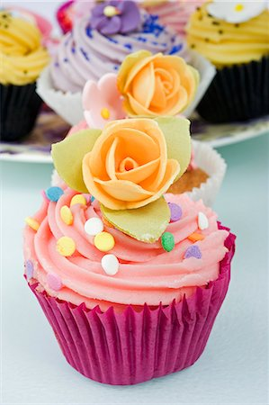sweet - still life of a row of coloured cup cakes decorated with orange rose flowers on top in their cake papers on a white table with other cup cakes in the background Stock Photo - Premium Royalty-Free, Code: 659-06903190