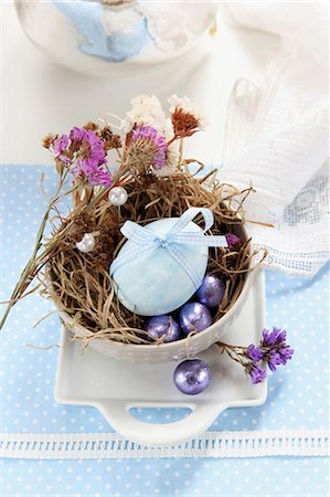 An egg decorated with a ribbon, dried flowers and chocolate eggs in an Easter nest made of moss and grass Stock Photo - Premium Royalty-Free, Code: 659-06903498