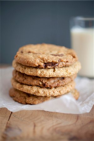 Chocolate chip, peanut butter and oatmeal cookies stacked on baking parchment wih a glass of milk in the background. Stock Photo - Premium Royalty-Free, Code: 659-06903530