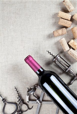 A bottle of red wine, old corkscrews and wine corks Stock Photo - Premium Royalty-Free, Code: 659-06903600